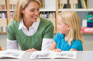 B4N4KG Student in class reading with teacher